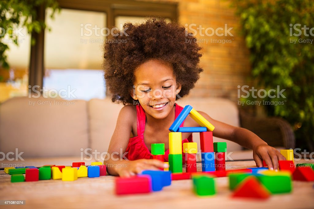 Happy little Afro girl palying with colourful building blocks stock photo