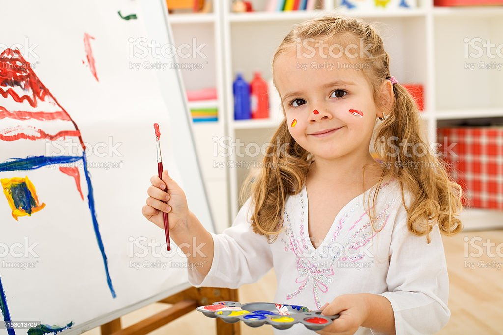 Happy little artist - girl painting a house royalty-free stock photo