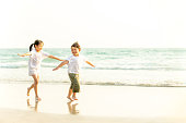 Little asian brother and sister having fun together on the beach at summer sunset.
