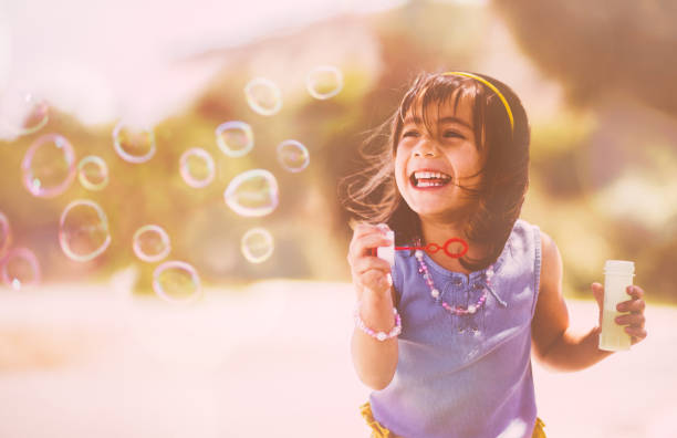 Happy little Asian girl blowing bubbles at the playground stock photo