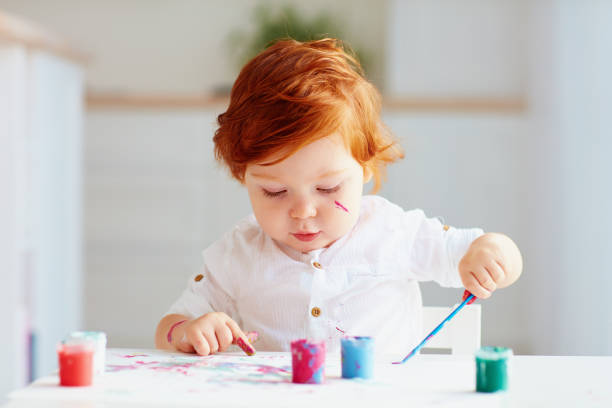 happy little baby artist drawing with colorful paints at home stock photo