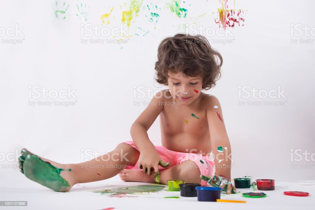 Happy little baby boy painting with his hands. stock photo