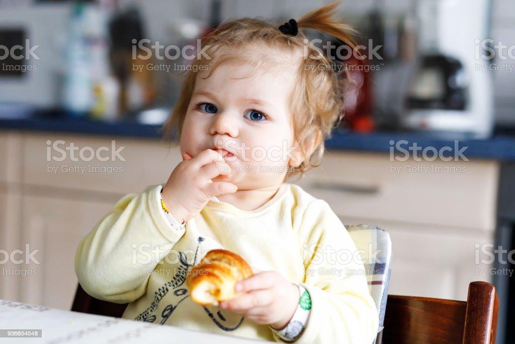 Glückliches kleines Mädchen essen frischen Croissant zum Frühstück oder Mittagessen. Gesunde Ernährung für Kinder – Foto