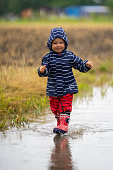 happy little baby girl running through puddle on rainy day