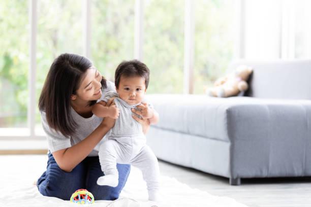 Happy little baby learning to walk with mother help in living room picture id1267700628?b=1&k=6&m=1267700628&s=612x612&w=0&h=n1zezvkmjc3wabvddvajsxmvhgvw63mjdeeksi2vuho=
