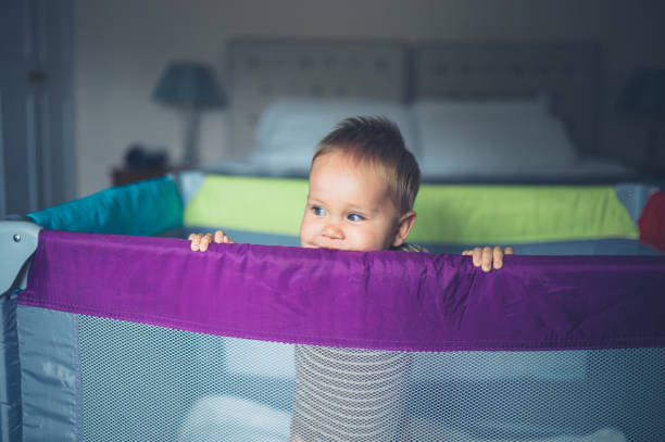 happy little baby standing in his pen - playpen stock pictures, royalty-free photos & images