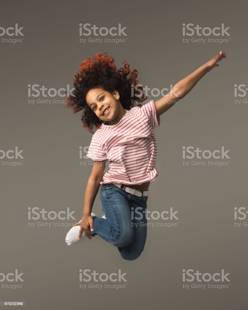 Happy little black girl jumping at studio background stock photo