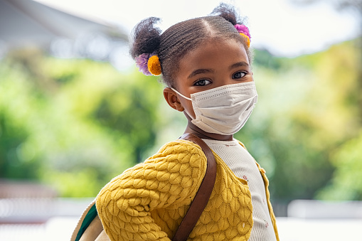 Smiling cute little girl with school backpack and protective face mask ready for first day of school during covid pandemic. African american female child wearing surgical mask while looking at camera. Cute black kid going back to school during coronavirus pandemic disease.