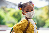 istock Happy little black girl with face mask ready to go to elementary school 1308840815