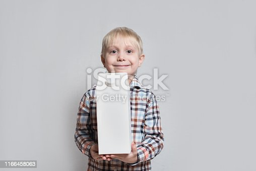 istock Happy little blond boy is holding a big white carton package. Light background. 1166458063