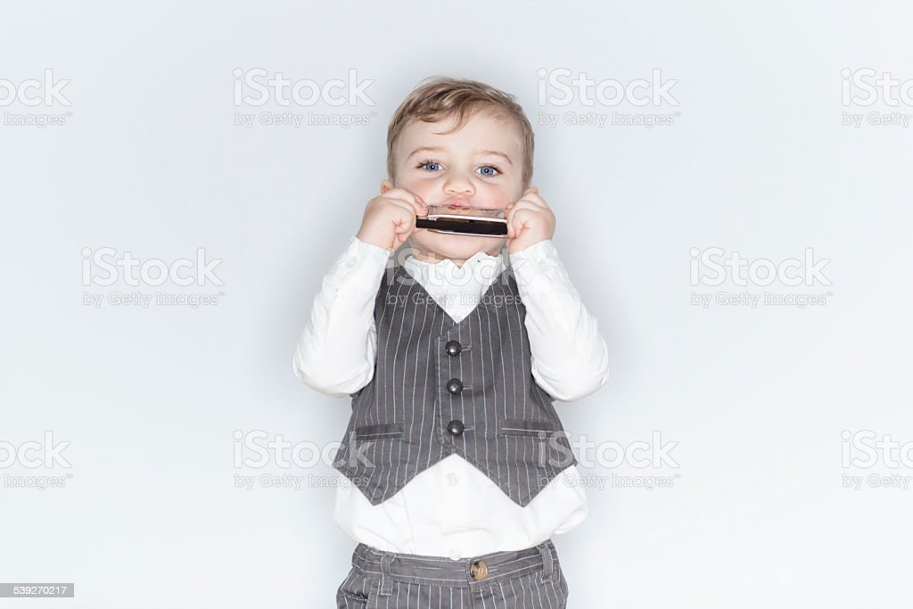 happy little blond boy with a harp stock photo