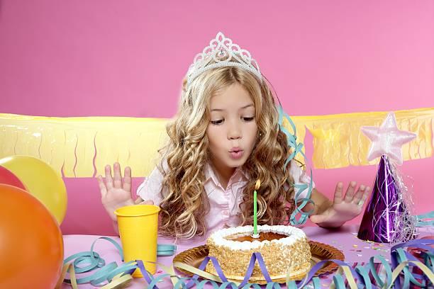 glückliches kleines blondes mädchen blasen kuchen kerzen auf geburtstag party - prinzessinnen torte stock-fotos und bilder
