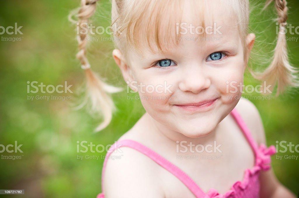 Happy Little Blonde Girl Smiling Outside stock photo