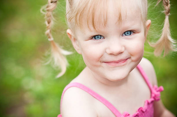 happy little blonde girl smiling outside - pigtails stock photos and pictures
