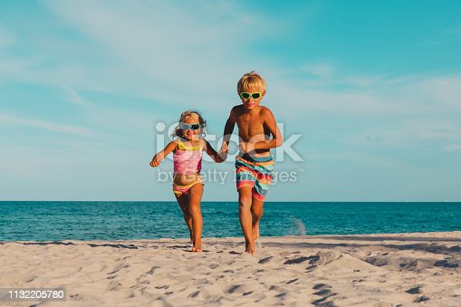 istock happy little boy and girl running at beach 1132205780