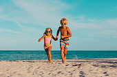 happy little boy and girl running at beach, family vacation at sea