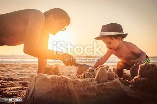 509423868 istock photo Happy little boy and his father building sandcastle on the beach 1141672900