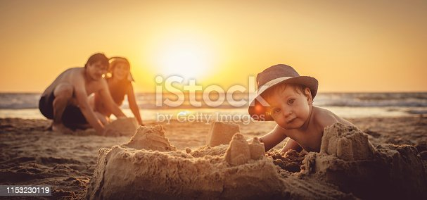 512726470 istock photo Happy little boy and his father building sandcastle on the beach 1153230119