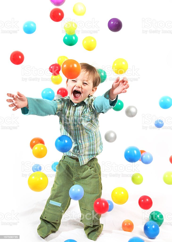 Happy little boy being rained on by colored balls royalty-free stock photo