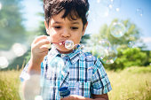 Close up portrait of happy little boy blowing bubbles outdoors.Mixed race boy.