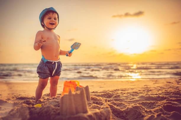 heureux petit garçon construction de châteaux de sable sur la plage au coucher du soleil - chateau de sable photos et images de collection