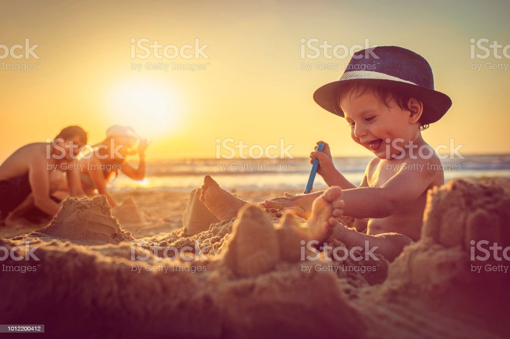 Happy little boy building sandcastle on the beach stock photo