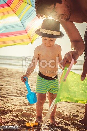 509423868 istock photo Happy little boy building sandcastle on the beach 1141672845