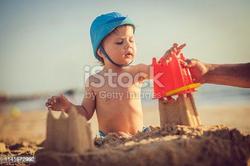 509423868 istock photo Happy little boy building sandcastle on the beach 1141672992