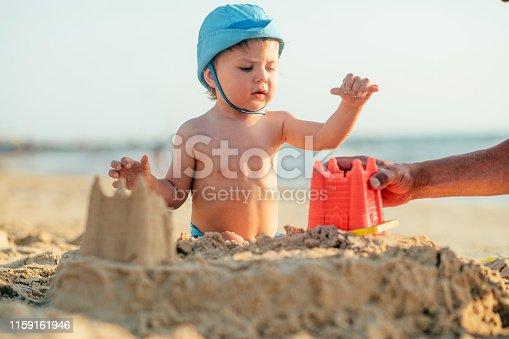 509423868 istock photo Happy little boy building sandcastle on the beach 1159161946