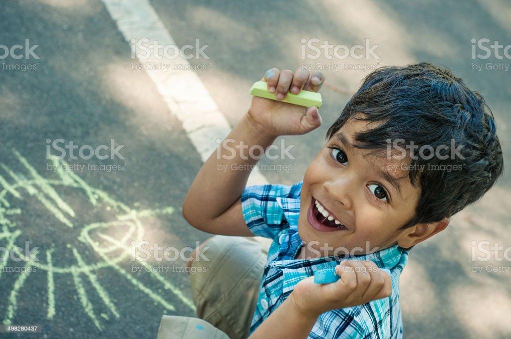 Happy little boy chalking stock photo