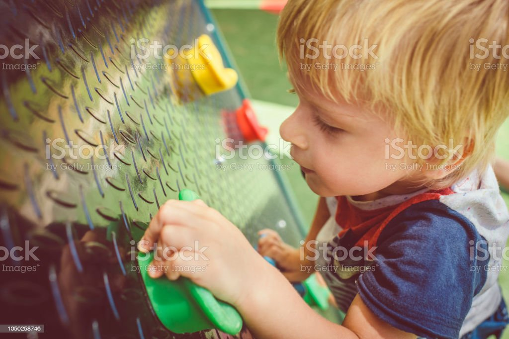 Happy little boy climbing in playground stock photo