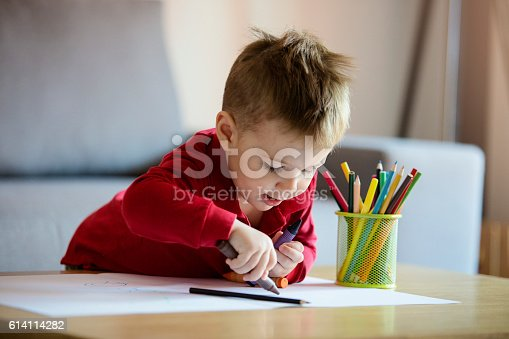 istock Happy little boy coloring 614114282