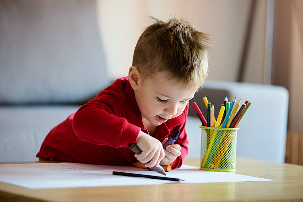 Happy little boy coloring stock photo