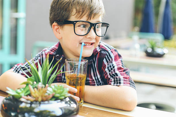 happy little boy drinking soda drink - nerd boy eating stock photos and pictures