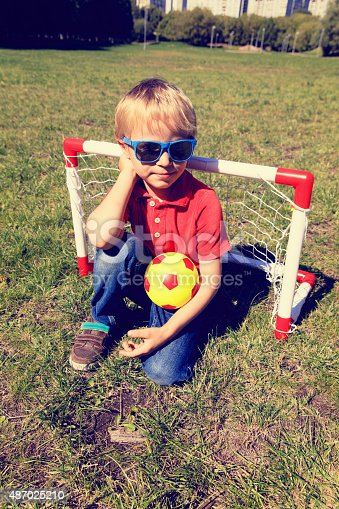 621475196 istock photo happy little boy enjoy playing football 487025210