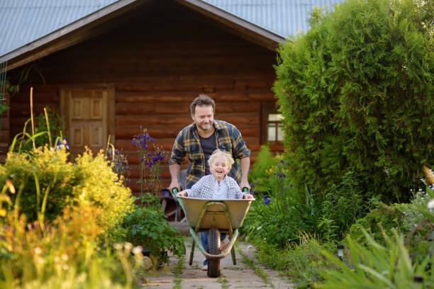 Feliz niño que se divierte en una carretilla empujando por papá en el jardín doméstico en el día cálido y soleado. - foto de stock
