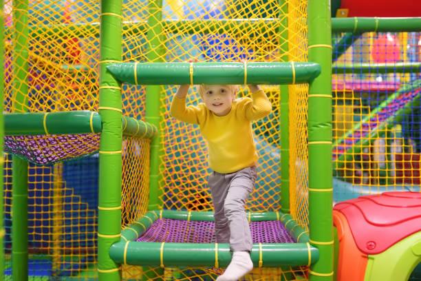Feliz niñito divirtiéndose en diversión en el centro de juego. Niño jugando en el patio interior. - foto de stock
