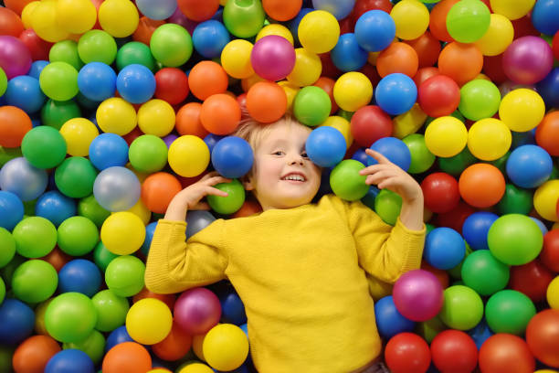 happy little boy having fun in ball pit with colorful balls. child playing on indoor playground. - playpen stock pictures, royalty-free photos & images