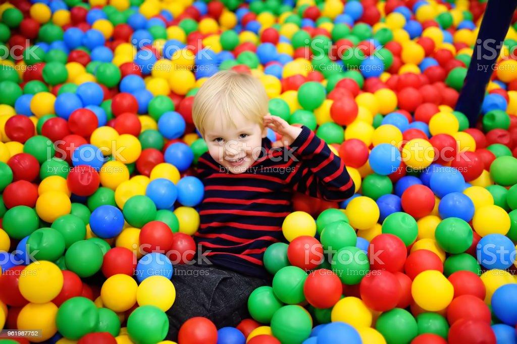Feliz niño divirtiéndose en el hoyo de la bola con las bolas de colores - foto de stock