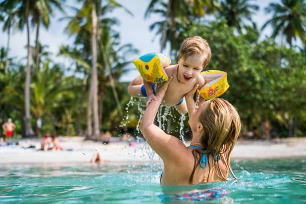 niño feliz divertirse en el mar mientras que siendo sostenido por su madre. - beach in thailand fotografías e imágenes de stock