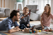 istock Happy little boy having fun with father and elder sister at home. 1216554264