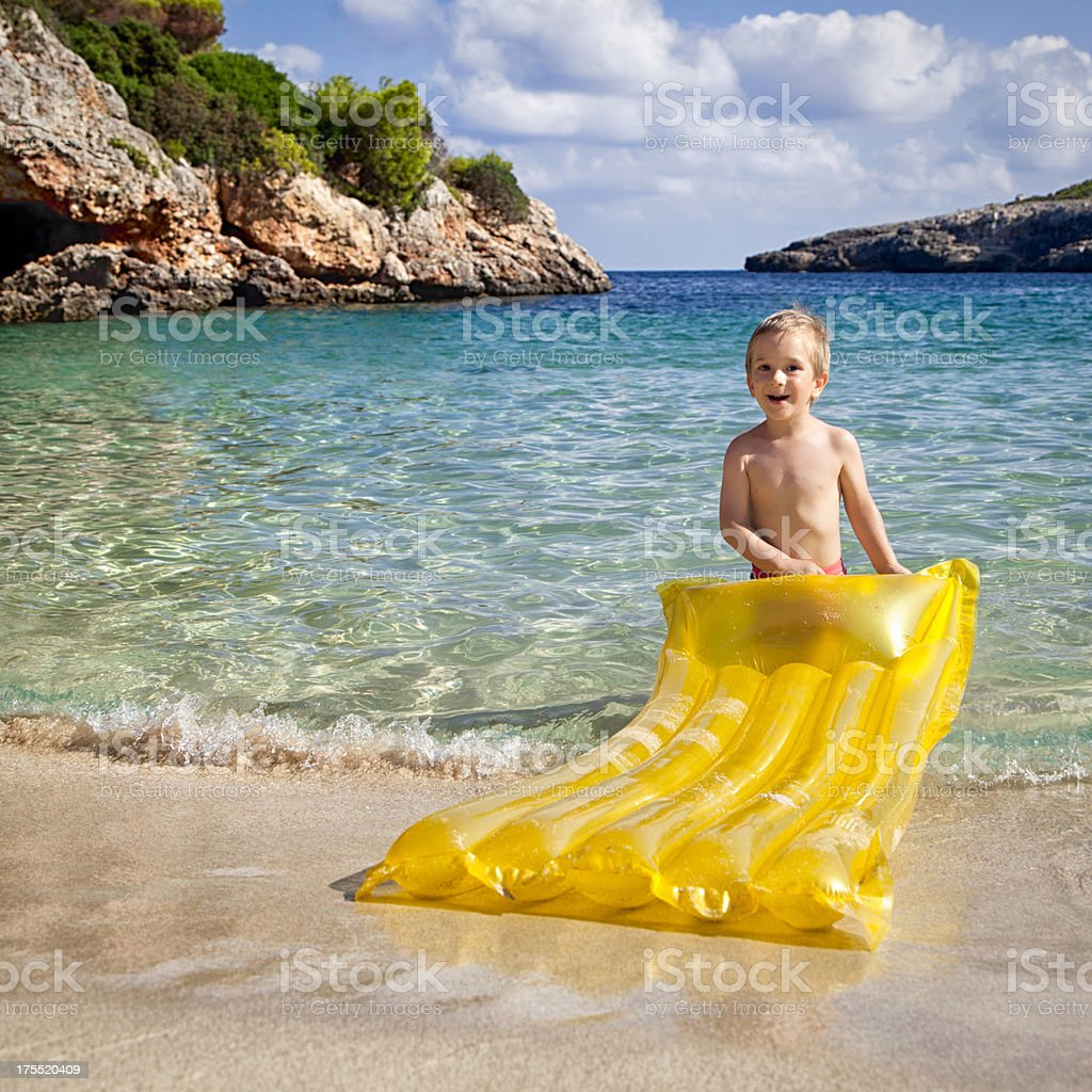 Happy Little Boy Holding Inflatable Air Bed on the Beach royalty-free stock photo