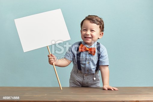 istock Happy little boy is holding a banner. 469874888