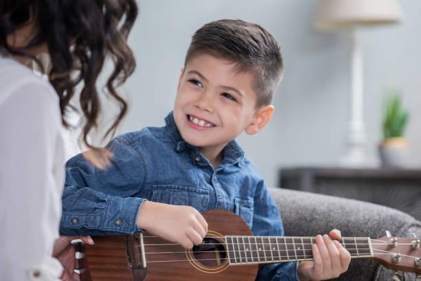 glücklicher kleiner junge ist während einer privaten musikunterricht mit mutter oder lehrer spielt ukulele üben. - ukulele songs stock-fotos und bilder