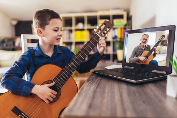 Happy little boy learning to play guitar while watching lessons at laptop at home stock photo