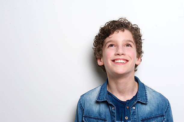 happy little boy looking up Close up portrait of a happy little boy looking up on white background 12 13 years stock pictures, royalty-free photos & images