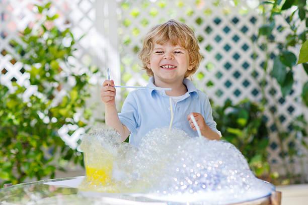 glückliche kleine junge, die mit farbenfrohen wasser und seife - versuche nicht zu lachen stock-fotos und bilder