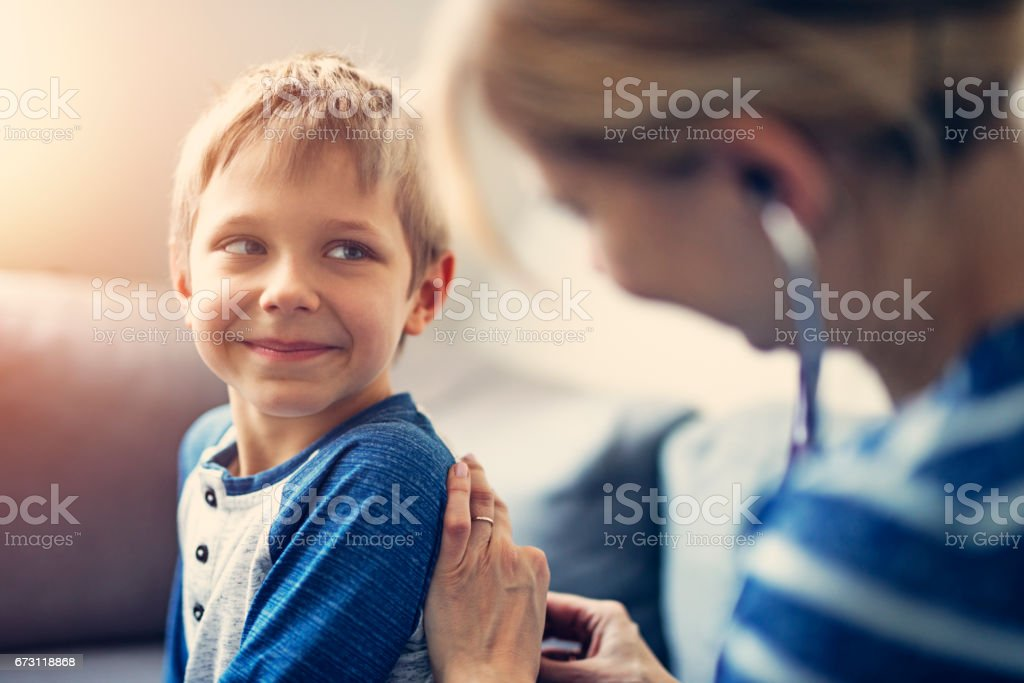 Happy little boy medical examination at home stock photo