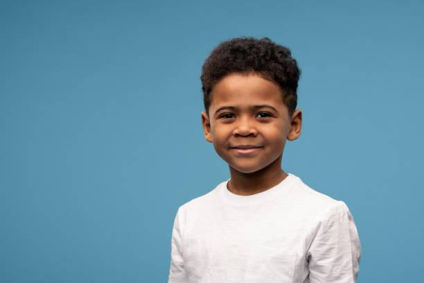 menino feliz da etnia africana em camiseta em pé na frente da câmera - lifestyle color background - fotografias e filmes do acervo