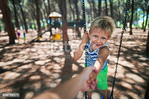 istock Happy little boy on swing pulled by father 639788370